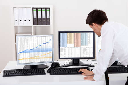 Over the shoulder view of the computer screens of a stock broker trading in a bull market showing ascending graphs
