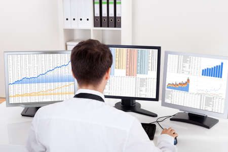 financial analysis: Over the shoulder view of the computer screens of a stock broker trading in a bull market showing ascending graphs Stock Photo