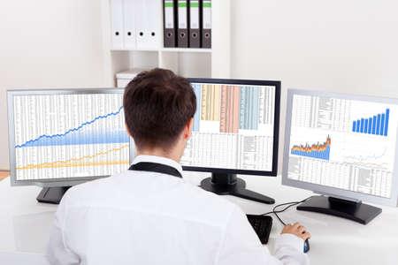 agente comercial: Vista por la espalda de las pantallas de las computadoras de un corredor de bolsa de comercio en un mercado alcista que muestran los gráficos ascendentes Foto de archivo