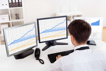 equity: Over the shoulder view of the computer screens of a stock broker trading in a bull market showing ascending graphs Stock Photo