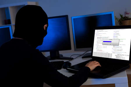 Masked hacker wearing a balaclava sitting at a desk downloading private information off a computer Stock Photo - 17384506