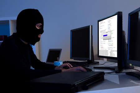 Álarcos hacker viselt maszkot ül egy asztal letöltés privát adatokat egy számítógép