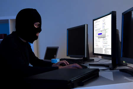 Masked hacker wearing a balaclava sitting at a desk downloading private information off a computer photo