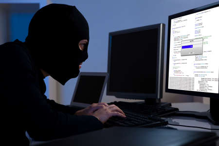 breach: Masked hacker wearing a balaclava sitting at a desk downloading private information off a computer