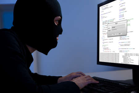 Masked hacker wearing a balaclava sitting at a desk downloading private information off a computer Stock Photo - 17384501