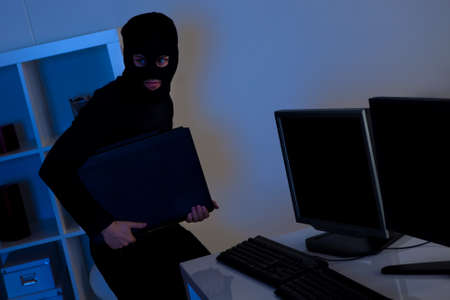 Man dressed in black and wearing a balaclava is stealing a laptop from an office Stock Photo - 17379571