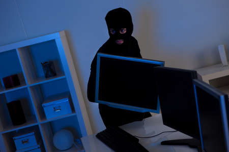 Man dressed in black and wearing a balaclava is stealing a laptop from an office photo