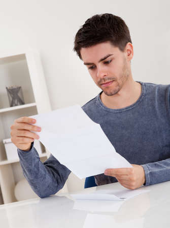 Exultant young man cheering at good news he has just received in a document that he is reading Stock Photo - 17384573