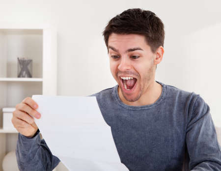received: Exultant young man cheering at good news he has just received in a document that he is reading Stock Photo