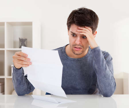 aghast: Horrified young man reading a document with an aghast expression and his hand to his forehead as he stares wide eyed at the page of paper