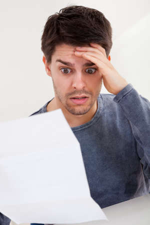 Horrified young man reading a document with an aghast expression and his hand to his forehead as he stares wide eyed at the page of paper Stock Photo - 17384502