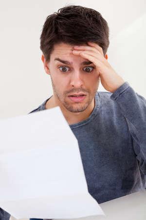 factura: Horrorizado hombre joven que lee un documento con una expresi�n horrorizada, y su mano a la frente mientras mira fijamente los ojos bien abiertos a la p�gina de papel