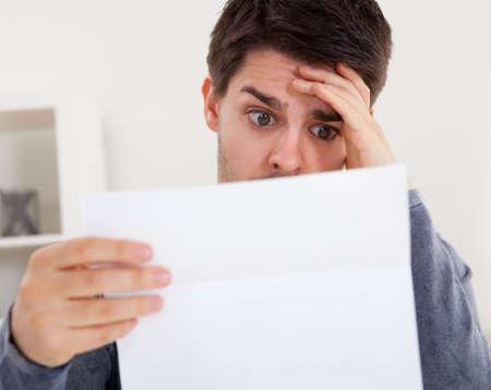 cuenta: Horrorizado hombre joven que lee un documento con una expresi�n horrorizada, y su mano a la frente mientras mira fijamente los ojos bien abiertos a la p�gina de papel
