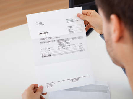 Overhead view of young man reading a invoice document Stock Photo - 17384509