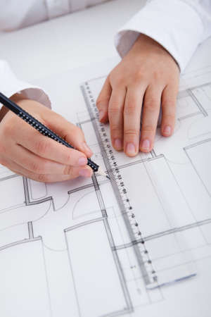 Closeup cropped image of a young male architect working on blueprints spread out on a table photo