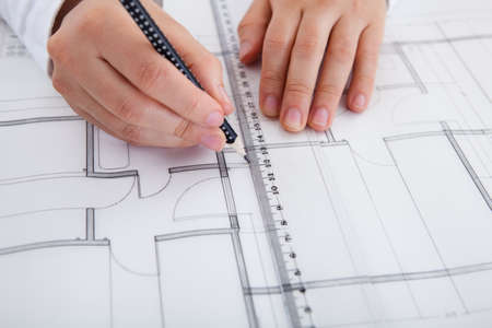 construction draftsman: Closeup cropped image of a young male architect working on blueprints spread out on a table Stock Photo
