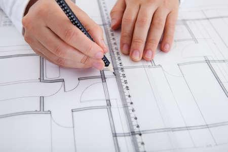 ingeniero civil: Closeup imagen recortada de un arquitecto masculino joven que trabaja en los planos extendidos sobre una mesa Foto de archivo