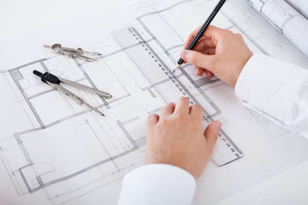 cropped image: Closeup cropped image of a young male architect working on blueprints spread out on a table Stock Photo