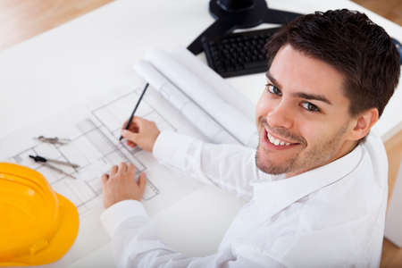 Closeup cropped image of a young male architect working on blueprints spread out on a table Stock Photo