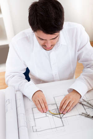 Closeup cropped image of a young male architect working on blueprints spread out on a table Stock Photo - 17384505
