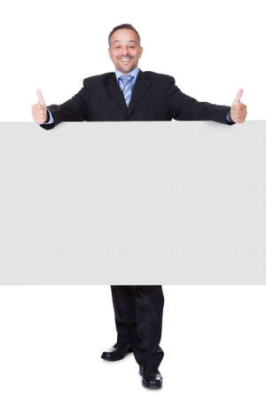 Happy Businessman Holding Blank Billboard On White Background photo