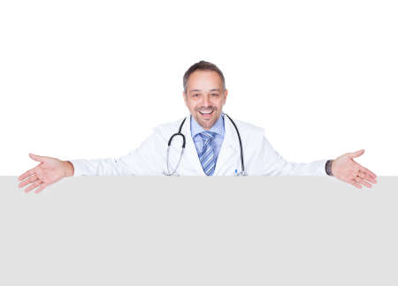 Portrait Of A Doctor Holding Blank Placard Isolated On White Background photo