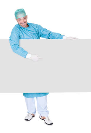 operation gown: Doctor In Operation Gown Holding Blank Placard On White Background