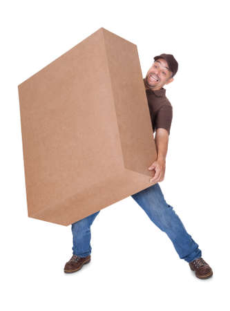 man carrying box: Delivery Man Carrying Heavy Box On White Background