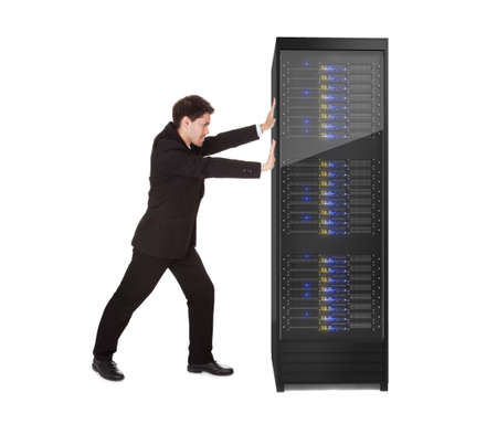 Businessman pushing server rack. Isolated on white Stock Photo - 17629928