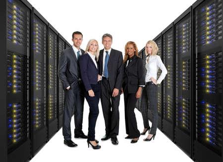 Businessteam staande op de voorkant van de twee lijnen van server racks. Geïsoleerd op witte achtergrond Stockfoto