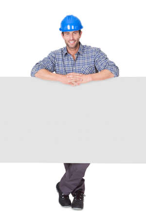 Portrait of happy worker presenting empty banner. Isolated on white photo