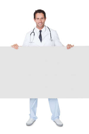 Portrait of friendly doctor presenting empty banner. Isolated on white photo