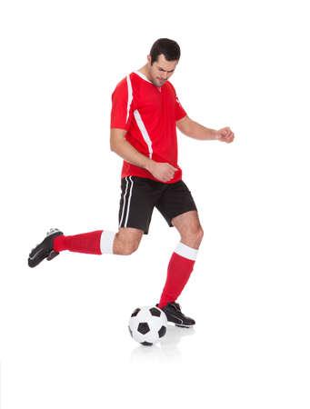 Striker: Profesjonalne piłkarz kopanie piłki. Samodzielnie na białym tle Zdjęcie Seryjne