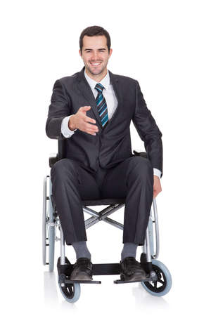 paraplegic: Young businessman in wheelchair. Isolated on white Stock Photo