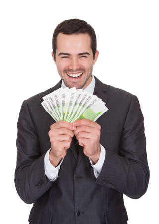 Excited businessman holding euro notes. Isolated on white photo