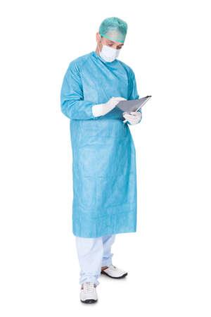 operation gown: Retrato Del Doctor En La Escritura Operaci�n Vestido En Carpeta Aislado En El Fondo Blanco Foto de archivo