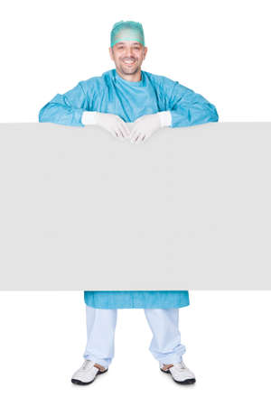 Doctor In Operation Gown Holding Blank Placard On White Background photo