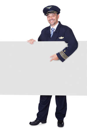 Portrait Of Happy Pilot Holding Blank Placard On White Background photo