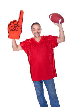 sport fan: Happy Man Wearing Foam Finger And Holding Rugby Ball On White Background