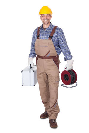 protective workwear: Happy Construction Worker Holding Toolbox And Cable On White Background