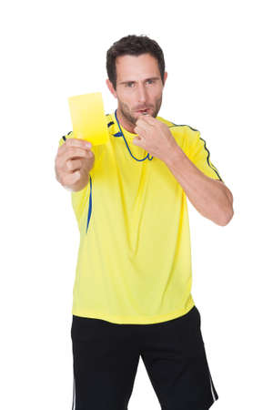 Soccer judge whistling and showing yellow card. Isolated on white Stock Photo - 17738795
