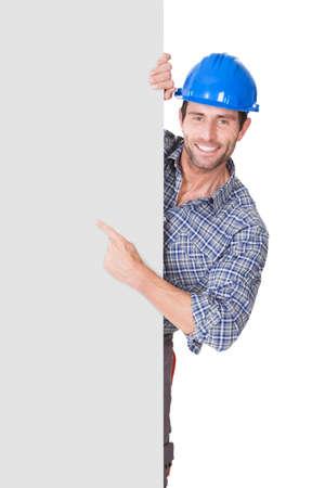 constructor: Retrato del trabajador feliz presentando bandera vac?a. Aislados en blanco