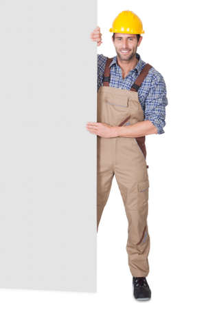 Portrait of happy construction worker presenting empty banner. Isolated on white photo