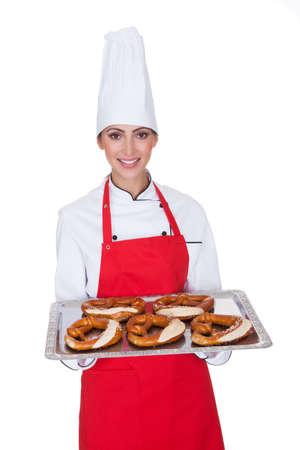 Female Baker Holding Fresh Bavarian Pretzel. Isolated On White photo