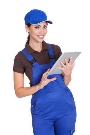 Smiling Female Plumber Working On Digital Tablet. Isolated On White photo