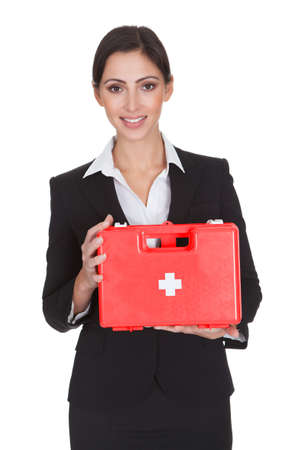 first aid box: Happy Businesswoman Holding First Aid Box. Isolated On White Stock Photo