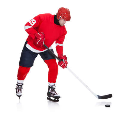 Professional hockey player skating on ice. Isolated on white photo