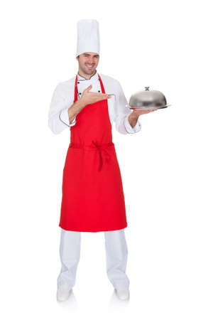 Portrait of cheerful chef presenting silver tray. Isolated on white photo