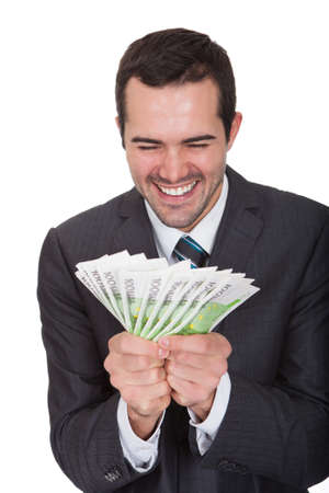 winning stock: Excited businessman holding euro notes. Isolated on white