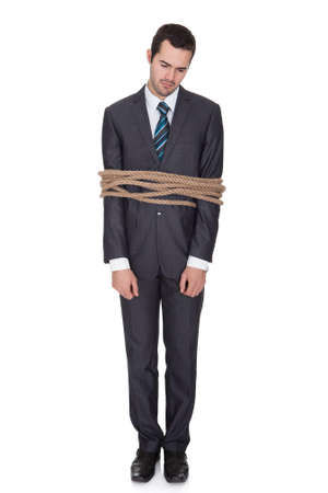 trapped: Businessman tied up in rope. Isolated on white Stock Photo